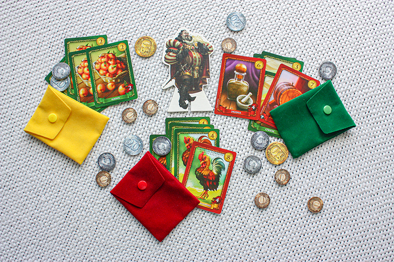 Sheriff of Nottingham board game, showing the cards, coins, pouches, and other pieces of the game.