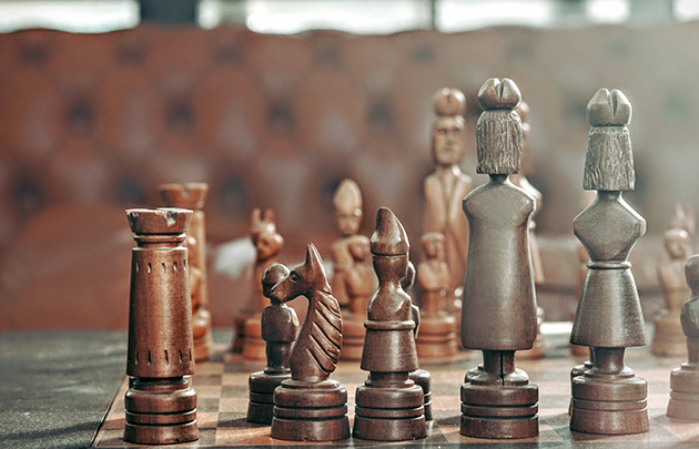 Wooden chess figures in their starting positions on the board